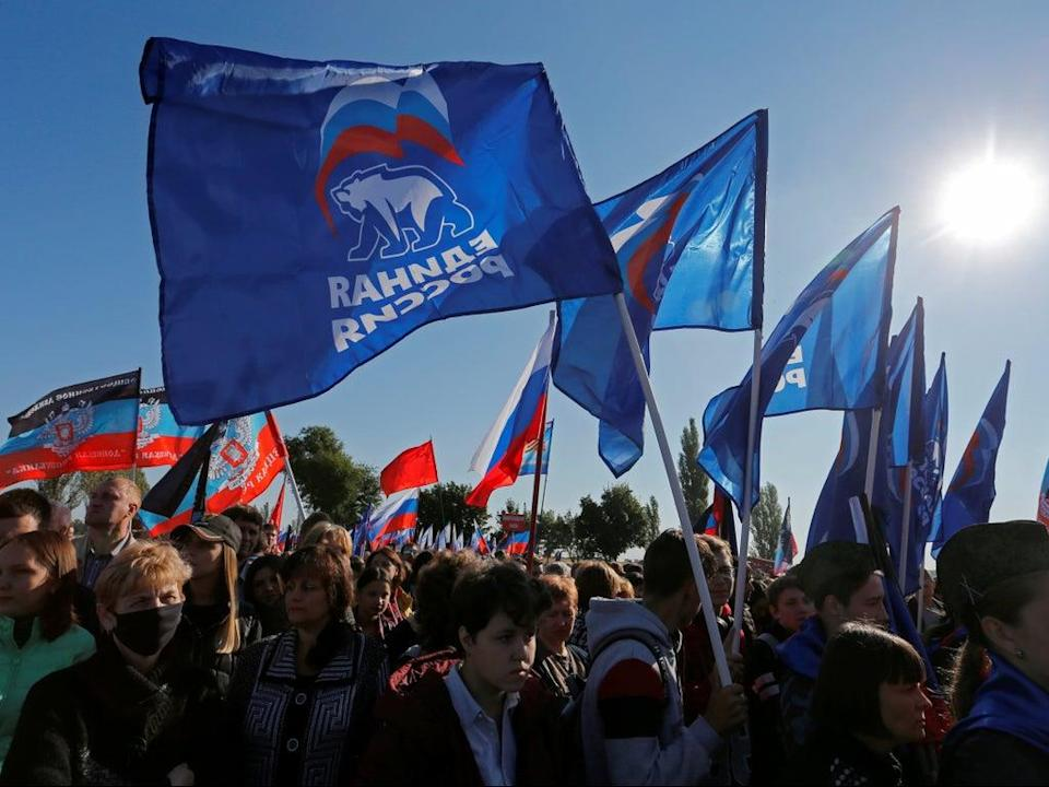 People hold flags of Russia's ruling United Russia party, during a rally at the war memorial complex Savur-Mohyla (REUTERS)