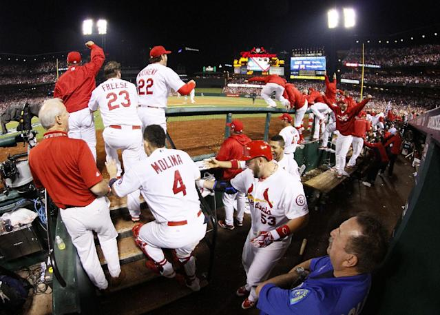 Cardinals players in the dugout react after Carlos Beltran hit the game-winning single in the bottom of the 13th inning during Game 1 of the National League Championship Series between the St. Louis Cardinals and the Los Angeles Dodgers on Friday, Oct. 11, 2013, at Busch Stadium in St. Louis. (AP Photo/St. Louis Post-Dispatch, Chris Lee)