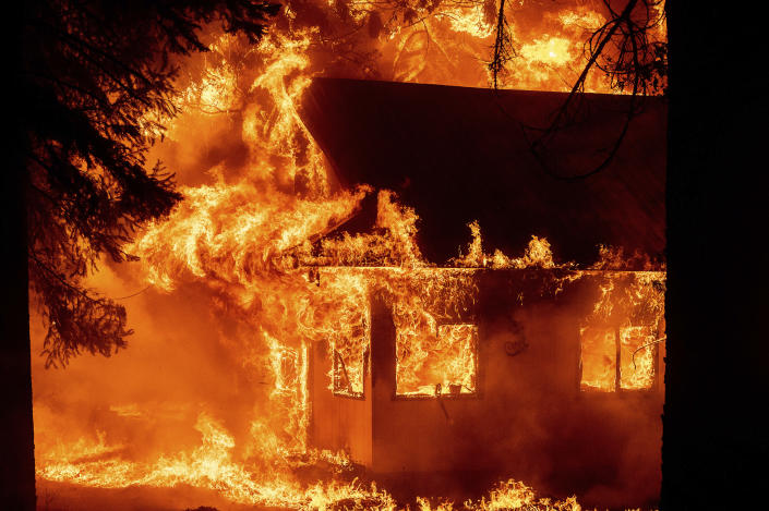 Flames consume a home as the Dixie Fire tears through the Indian Falls community in Plumas County, Calif., on Saturday, July 24, 2021. The fire destroyed multiple residences in the area. (AP Photo/Noah Berger)