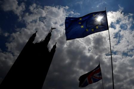 An EU flag and a British Union Jack flag are seen flying near the Houses of Parliament in London