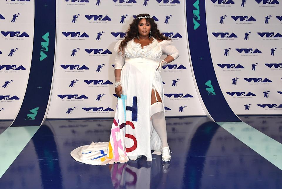 """Lizzo was a vision in white as she arrived at the MTV Music Awards in Seth Pratt with the title of her popular song, """"Truth Hurts,"""" embroidered on her train in multicolored letters. A look for the books."""