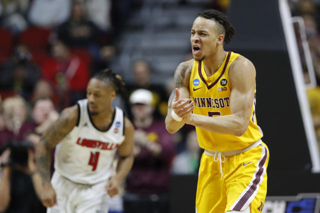 Minnesota guard Amir Coffey, right, celebrates in front of Louisville guard Khwan Fore, left, after making a basket during a first round men's college basketball game in the NCAA Tournament, Thursday, March 21, 2019, in Des Moines, Iowa. (AP Photo/Charlie Neibergall)