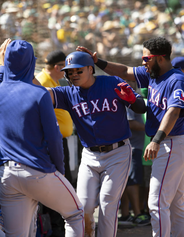 Texas Rangers Shin-Soo Choo, center, is greeted by his teammates after scoring on a single by Danny Santana during the fourth inning of a baseball game against the Oakland Athletics, Sunday, Sept. 22, 2019, in Oakland, Calif. (AP Photo/D. Ross Cameron)