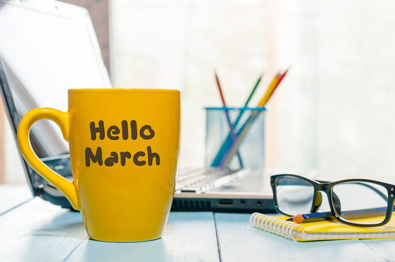 Coffee cup that says Hello March on a desk next to a computer, eyeglasses, a pad, and a pencil holder.