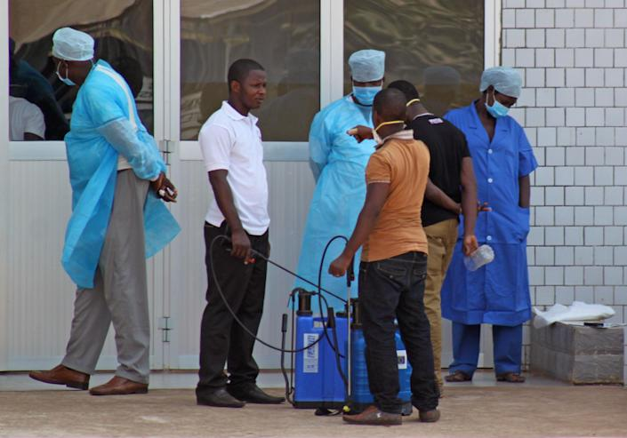 In this photo taken on Saturday, March 29, 2014, medical personnel at the emergency entrance of a hospital receive suspected Ebola virus patients in Conakry, Guinea. Senegal has closed its land border with neighboring Guinea to prevent the spread of the Ebola outbreak, which has killed at least 70 people. Senegal's Interior Ministry announced the border closure Saturday. It also said officials in the southern region of Kolda closed a weekly market which draws thousands of people from the neighboring West African countries of Guinea, Gambia and Guinea-Bissau. Guinea confirmed last week that several victims of hemorrhagic fever in the country's southern region had tested positive for Ebola. (AP Photo/ Youssouf Bah)