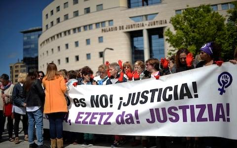 "Protesters gather outside the High Court of Navarra behind a banner reading ""No is No! Justice!""  - Credit: Reuters"