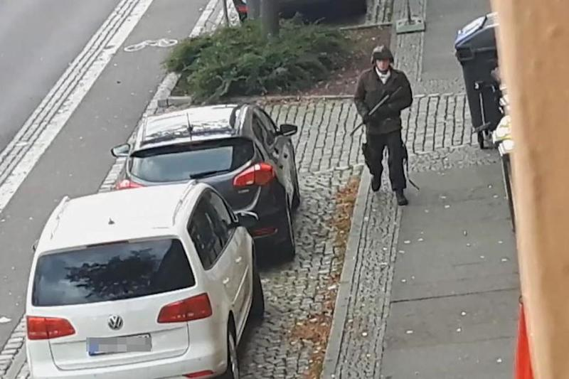 The suspect walks with a gun in the streets of Halle, eastern Germany (ATV-Studio Halle/AFP via Getty)
