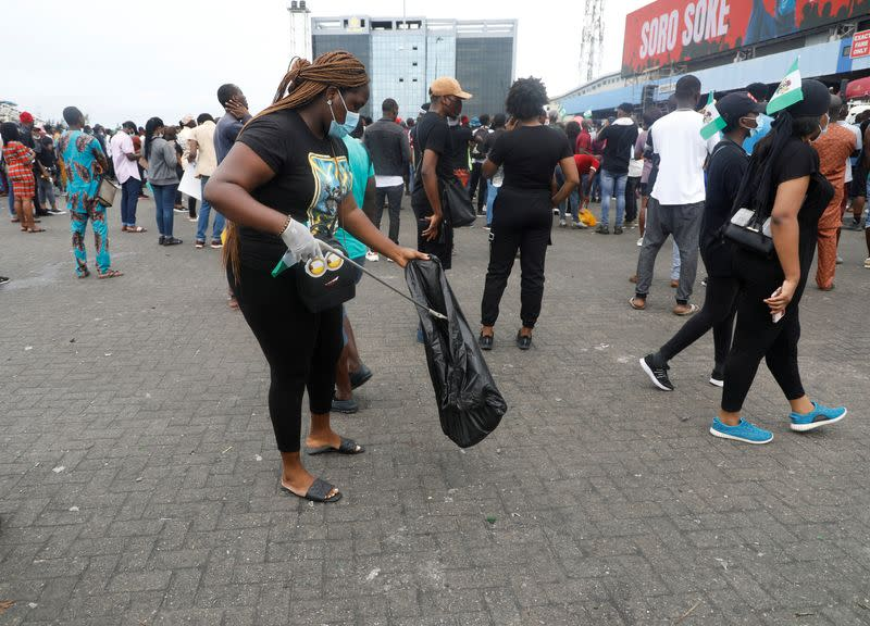 A demonstrator picks up litter from the street during a protest over police brutality in Lagos