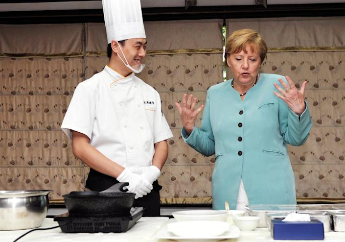 Angela Merkel learns how to make kung pao chicken from a cook at a restaurant in Chengdu, southwest China's Sichuan province on July 6, 2014 (AFP Photo/AFP)