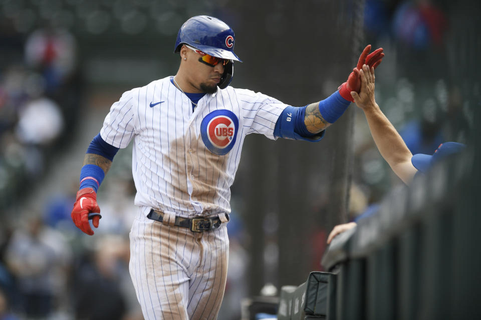 Chicago Cubs' Javier Baez celebrates at the dugout with manager David Ross after hitting a solo home run during the second inning of a baseball game against the Milwaukee Brewers, Friday, April 23, 2021, in Chicago. (AP Photo/Paul Beaty)
