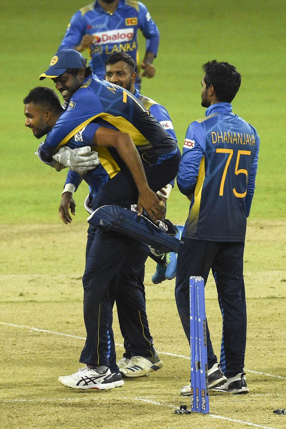 Sri Lanka's cricket captain Dasun Shanaka (L) celebrates with his teammates after the dismissal India's Manish Pandey (not pictured) during the second one-day international (ODI) cricket match between Sri Lanka and India at the R.Premadasa Stadium in Colombo on July 20, 2021. (Photo by Ishara S. KODIKARA / AFP) (Photo by ISHARA S. KODIKARA/AFP via Getty Images)