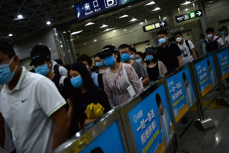 People wearing face masks commute inside a subway station during morning rush hour, following new cases of coronavirus disease (COVID-19) infections in Beijing