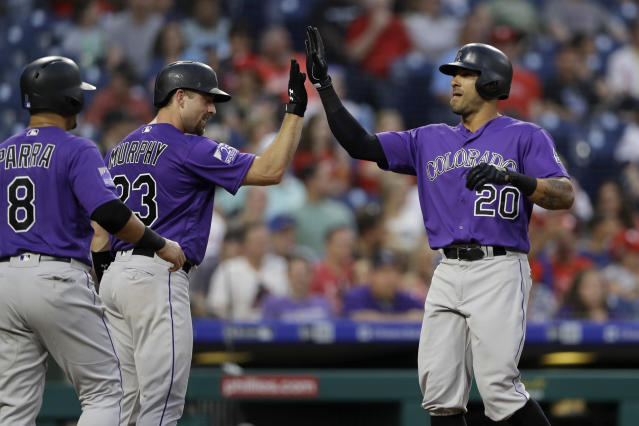 Colorado Rockies' Ian Desmond (20) celebrates with Tom Murphy (23) and Gerardo Parra (8) after Desmond's two-run home run off Philadelphia Phillies starting pitcher Nick Pivetta during the fourth inning of a baseball game Wednesday, June 13, 2018, in Philadelphia. (AP Photo/Matt Slocum)