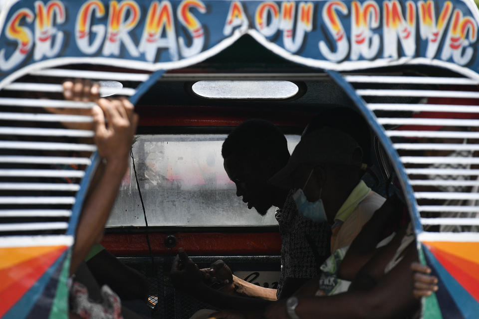 """Commuters travel on a bus popularly referred to as """"tap-tap"""" in Port-au-Prince, Haiti, Thursday, July 15, 2021, just over a week since Haitian President Jovenel Moise was assassinated in his home. Authorities in Haiti on Thursday forcefully pushed back against reports that current government officials were involved in the killing of Haitian President Jovenel Moïse, calling them """"a lie."""" (AP Photo/Matias Delacroix)"""