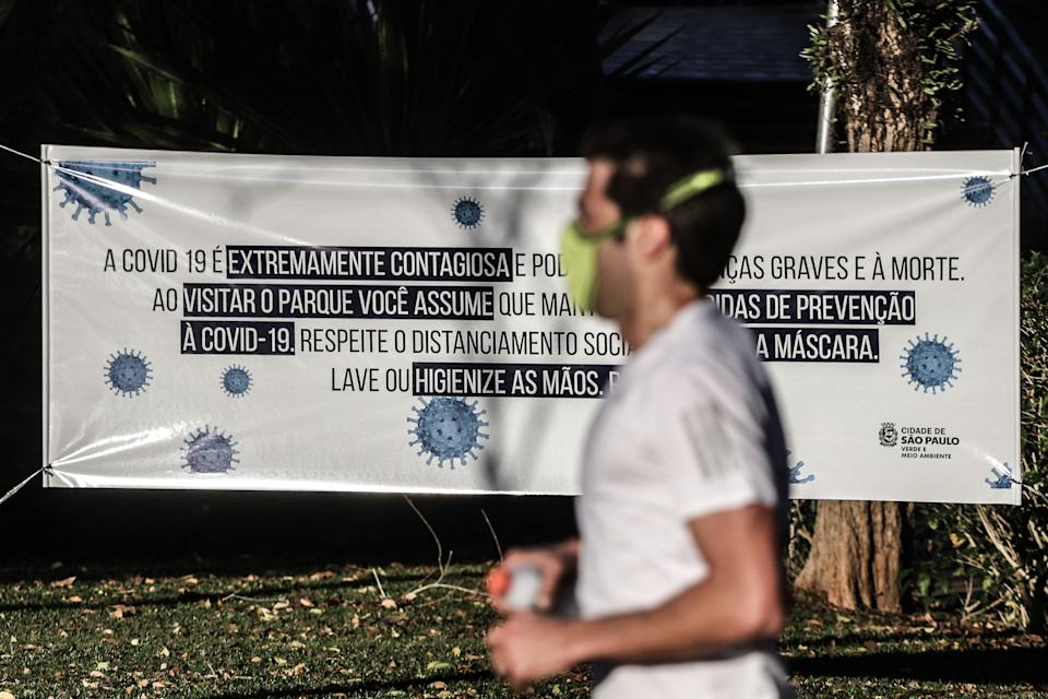 SAO PAULO, July 14, 2020  -- A citizen jogs past a banner with COVID-19 safety tips at the reopened Ibirapuera Park in Sao Paulo, Brazil, July 13, 2020.   Brazil on Monday reported a total of 1,884,967 people have tested positive for COVID-19 and 72,883 people have died from the disease.    In the past day, tests detected 20,286 new cases of infection and 733 more patients died, according to the Health Ministry. (Photo by Rahel Patrasso/Xinhua via Getty) (Xinhua/ via Getty Images)