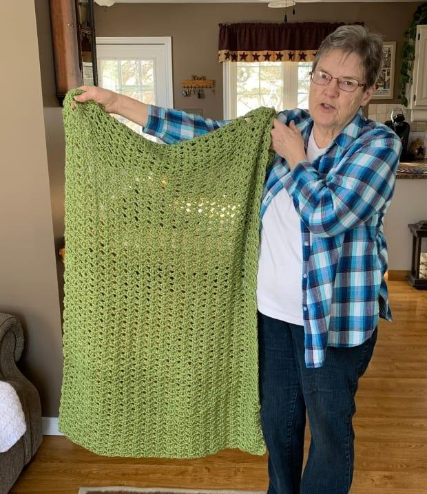 Marilyn Lerette holds up an example of a prayer shawl. This one was made by Erma Black. Members of Heart and Hands say they use only soft yarn that they buy themselves to make sure the shawls are comfortable.