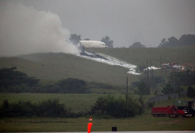 A UPS cargo plane lies on a hill at Birmingham-Shuttlesworth International Airport after crashing on approach, Wednesday, Aug. 14, 2013, in Birmingham, Ala. Toni Herrera-Bast, a spokeswoman for Birmingham's airport authority, says there are no homes in the immediate area of the crash. (AP Photo/Hal Yeager)