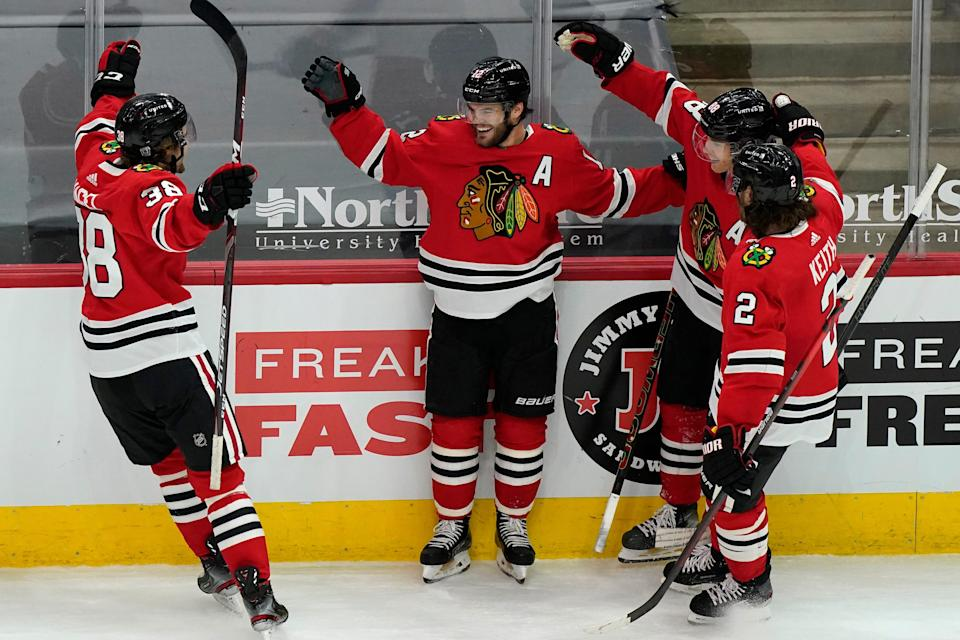 Chicago Blackhawks' Alex DeBrincat, second from left, celebrates with teammates Brandon Hagel, left, Duncan Keith, right, and Patrick Kane after scoring the winning goal against the Columbus Blue Jackets during the overtime period of an NHL hockey game in Chicago, Saturday, Feb. 13, 2021. (AP Photo/Nam Y. Huh)