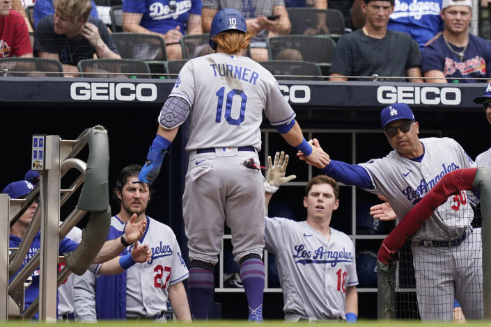 Los Angeles Dodgers' Justin Turner (10) is greeted by manager Dave Roberts (30) as he returns to the dugout after scoring on an Albert Pujols base hit in the fourth inning of a baseball game against the Atlanta Braves, Sunday, June 6, 2021, in Atlanta. (AP Photo/Brynn Anderson)