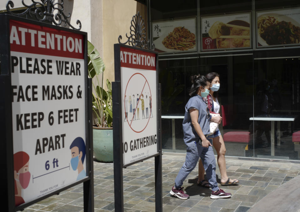 FILE - In this June 11, 2021, file photo, customers wear face masks in an outdoor mall with closed business amid the COVID-19 pandemic in Los Angeles. The latest alarming coronavirus variant, the delta variant, is exploiting low global vaccination rates and a rush to ease pandemic restrictions, adding new urgency to the drive to get more shots in arms and slow its supercharged spread. (AP Photo/Damian Dovarganes, File)