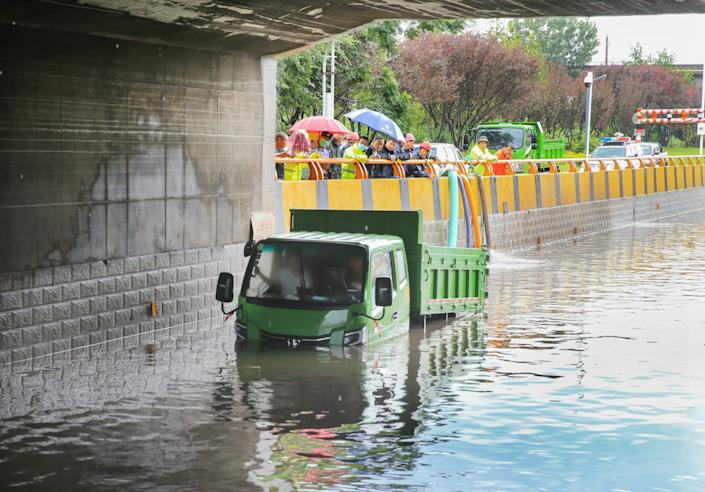 A small green dumptruck is stranded in high water below a bridge while pedestrians with umbrellas stand and watch.