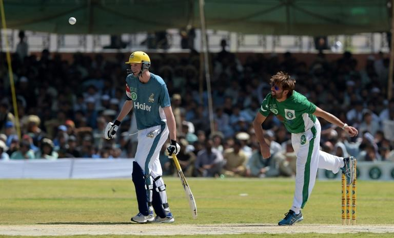 Pakistan XI bowler Shahid Afridi (R) delivers a ball next to UK Media XI batsman during a T20 cricket match between Pakistan XI and UK Media XI at the Younis Khan Cricket Stadium in Miranshah, the former stronghold of Al-Qaeda and Taliban militants