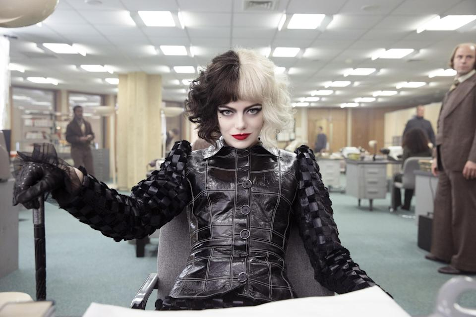 Emma Stone looks at the camera seated across the desk