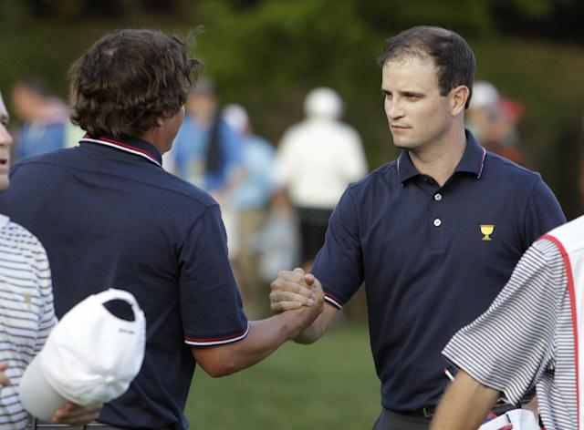 United States team player Zach Johnson, right, shakes hands with teammate Jason Dufner after winning 5 and 3 in a four-ball match against the International's Branden Grace and Richard Sterne at the Presidents Cup golf tournament at Muirfield Village Golf Club Thursday, Oct. 3, 2013, in Dublin, Ohio. (AP Photo/Jay LaPrete)