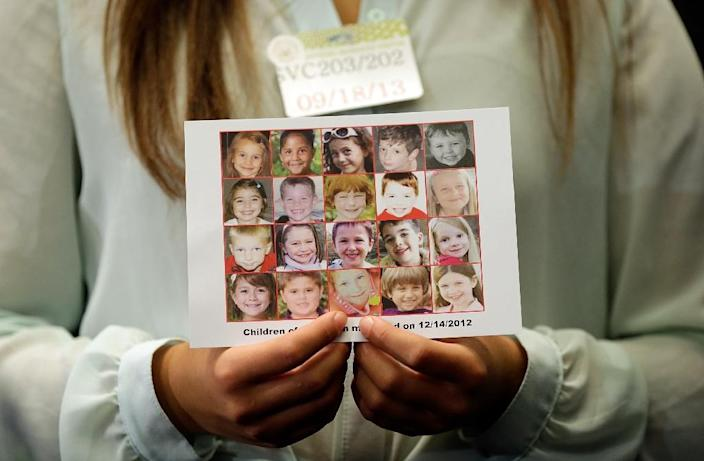 A woman displays a photo of the children killed in the Sandy Hook shooting during a September 2013 press conference in Washington calling for gun reform legislation (AFP Photo/WIN MCNAMEE)