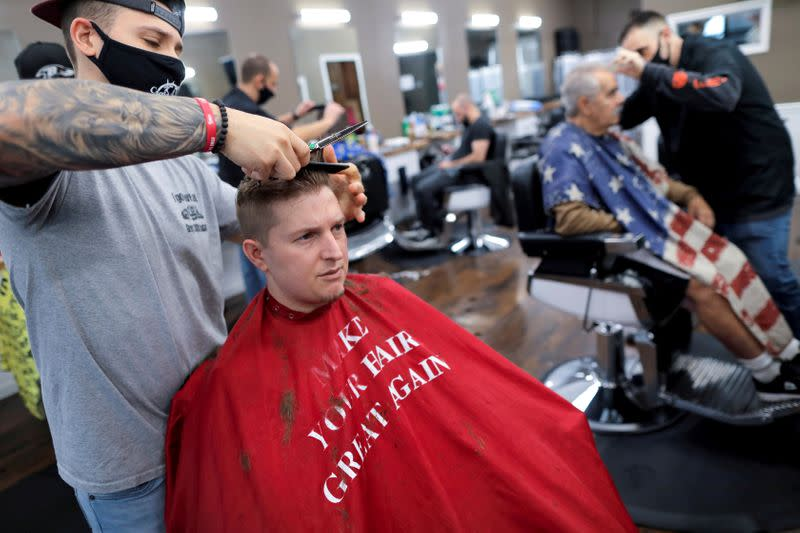 """FILE PHOTO: Aaron Schumacher, 33, of Staten Island has his hair cut at Craig & Pop's Barbershop while wearing a salon cape with a parody of U.S. President Donald Trump's """"Make America Great Again"""" phrase on Staten Island in New York City"""