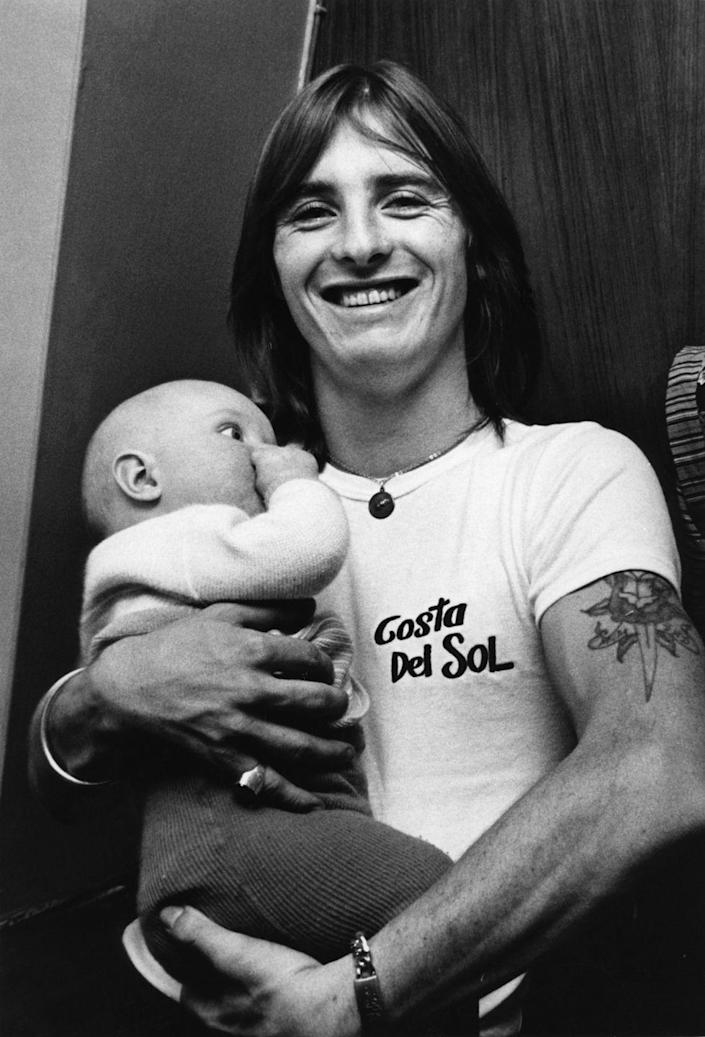 <p>AC/DC drummer, Phil Rudd, holds a baby backstage at one of their concerts. </p>