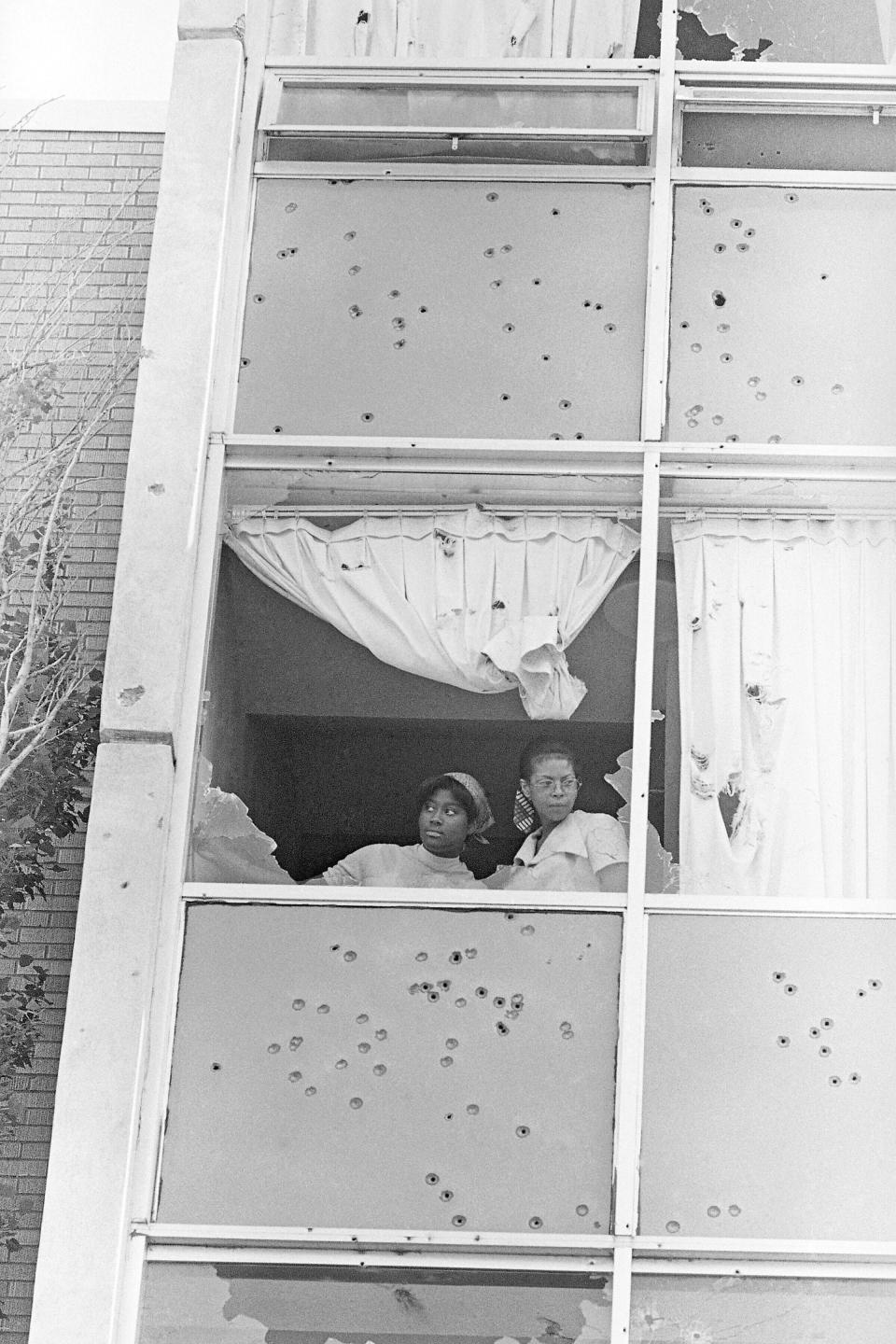 FILE - In this May 15, 1970, file photo, two students at Jackson State College, peer from a window at Alexander Hall, that was shot out by police on campus that morning, in Jackson, Miss. Two Black students died and 12 people were wounded as police shot indiscriminately, riddling the windows of the women's dormitory as officers claimed they had seen a sniper. The historically Black school canceled its 1970 commencement after the violent incident. Fifty-one years later, the school now called Jackson State University is honoring its Class of 1970, as members are being invited back to salute their academic achievements with a graduation ceremony Saturday, May 15, 2021. (AP Photo/Jack Thornell, File)