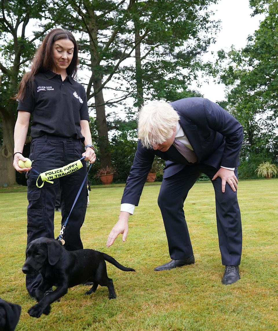 Prime Minister Boris Johnson speaks to police dog kennel staff during a visit to Surrey Police headquarters in Guildford, Surrey (Yui Mok/PA) (PA Wire)
