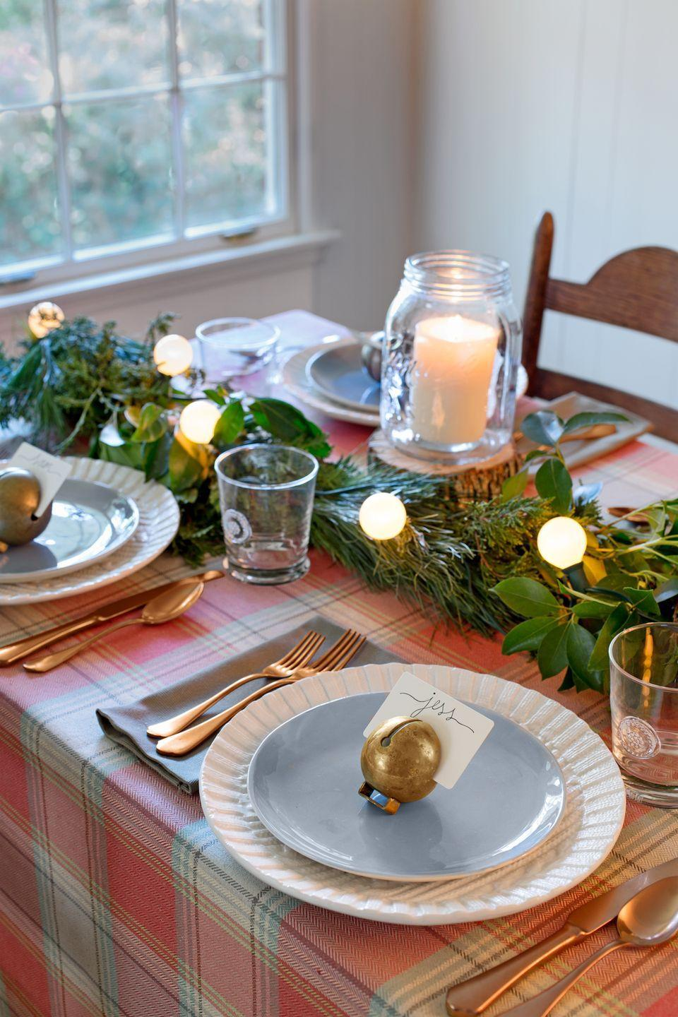 """<p>Look no further than your backyard for the makings of a pretty table runner, then add a pop of plaid with a classic tartan tablecloth. For a whimsical place setting, slide good old handwritten name cards into the slots of <a href=""""https://www.ebay.com/sch/i.html?_from=R40&_trksid=p2380057.m570.l1313.TR0.TRC0.H0.Xvintage+sleigh+bells.TRS0&_nkw=vintage+sleigh+bells&_sacat=0"""" rel=""""nofollow noopener"""" target=""""_blank"""" data-ylk=""""slk:vintage sleigh bells"""" class=""""link rapid-noclick-resp"""">vintage sleigh bells</a> (we found these <a href=""""http://www.ebay.com/itm/9-various-Vintage-solid-brass-sleigh-bells-Sizes-32-35mm-Rivet-mount-MMM-/332359103012"""" rel=""""nofollow noopener"""" target=""""_blank"""" data-ylk=""""slk:on eBay"""" class=""""link rapid-noclick-resp"""">on eBay</a>). Use candles in <a href=""""https://www.amazon.com/Ball-ounce-Jar-Wide-Mouth/dp/B01N1SIQP2/?tag=syn-yahoo-20&ascsubtag=%5Bartid%7C10050.g.2781%5Bsrc%7Cyahoo-us"""" rel=""""nofollow noopener"""" target=""""_blank"""" data-ylk=""""slk:oversized Mason jars"""" class=""""link rapid-noclick-resp"""">oversized Mason jars</a> and <a href=""""https://www.amazon.com/Flatware-Luxury-Stainless-Silverware-Service/dp/B01CNLZ6FW/?tag=syn-yahoo-20&ascsubtag=%5Bartid%7C10050.g.2781%5Bsrc%7Cyahoo-us"""" rel=""""nofollow noopener"""" target=""""_blank"""" data-ylk=""""slk:rose-gold flatware"""" class=""""link rapid-noclick-resp"""">rose-gold flatware</a>—both help to reinforce the warm, magical vibe. </p><p><a class=""""link rapid-noclick-resp"""" href=""""https://www.amazon.com/Ball-ounce-Jar-Wide-Mouth/dp/B01N1SIQP2/?tag=syn-yahoo-20&ascsubtag=%5Bartid%7C10050.g.2781%5Bsrc%7Cyahoo-us"""" rel=""""nofollow noopener"""" target=""""_blank"""" data-ylk=""""slk:SHOP MASON JARS"""">SHOP MASON JARS</a></p>"""