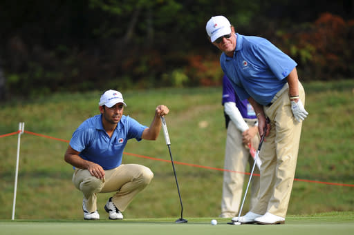 Denmark's Thorbjrn Olesen, left, lines up a putt next to Miguel Angel Jimenez of Spain on the second green during the first round of the Eurasia Cup golf tournament at the Glenmarie Golf and Country Club in Subang, Malaysia, Thursday, March 27, 2014. (AP Photo/Joshua Paul)