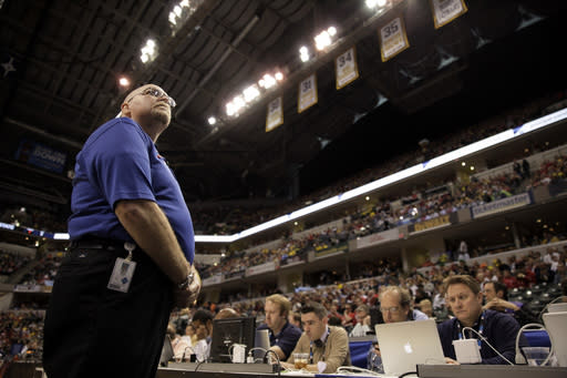In this photo taken on March 16, 2014, Bill Hefler, of ESG Security, looks up to the stands during a time out in the second half of an NCAA college basketball game between Ohio State and Michigan in the semifinals of the Big Ten Conference tournament in Indianapolis. Security firms charged with protecting college and professional sports venues are monitoring social media more than ever to prepare for everything from a garden-variety court storming to something much more dangerous. (AP Photo/Kiichiro Sato)