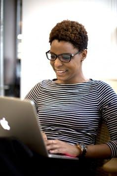 A woman sits with a laptop in a videoconference.