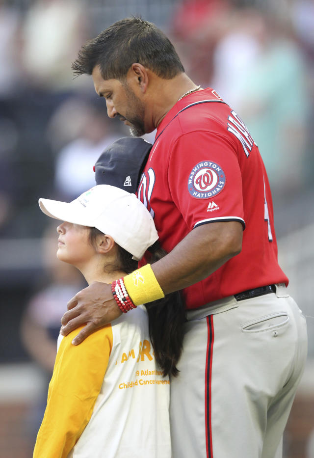 Washington Nationals manager Dave Martinez, right, puts his arm around cancer survivor 9-year-old Presley Taylor on Childhood Cancer Awareness Day prior to a baseball game against the Atlanta Braves, Saturday, Sept. 7, 2019, in Atlanta. (AP Photo/Tami Chappell)