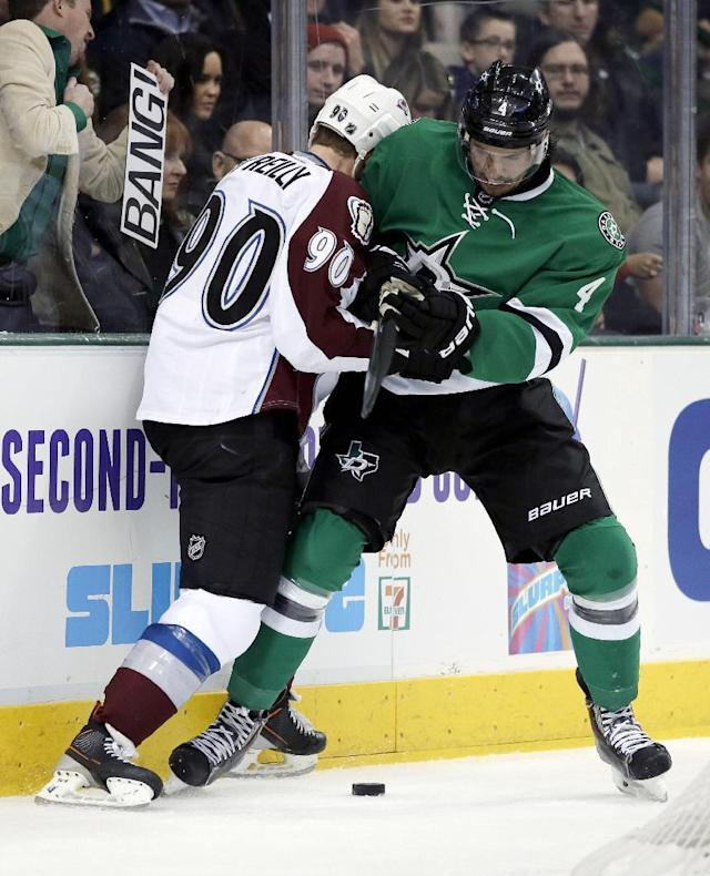 Dallas Stars' Brenden Dillon (4) and Colorado Avalanche's Ryan O'Reilly (90) compete for control of the puck behind the net in the second period of an NHL hockey game, Tuesday, Dec. 17, 2013, in Dallas. (AP Photo/Tony Gutierrez)