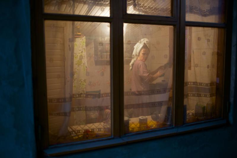 In this photo taken on Wednesday, Nov. 27, 2013, a woman washes up dishes in her kitchen in the yard of a house in the village of Vesyoloye, outside Sochi, Russia. As the Winter Games are getting closer, many Sochi residents are complaining that their living conditions only got worse and that authorities are deaf to their grievances.(AP Photo/Alexander Zemlianichenko)