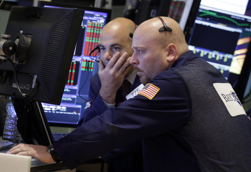A pair of traders work in their booth on the floor of the New York Stock Exchange Friday, Nov. 8, 2013. Stocks edged higher in early Friday trading as investors reacted to an unexpectedly strong October jobs report. (AP Photo/Richard Drew)