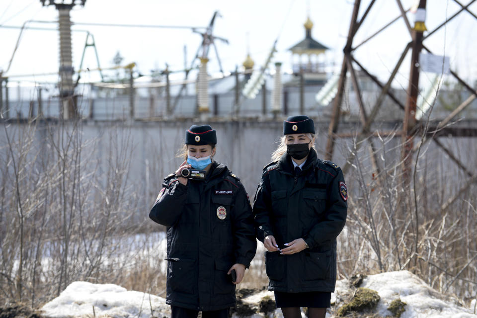 Police officers film as the Alliance of Doctors union's leader Anastasia Vasilyeva speaks to the media at the prison colony IK-2, which stands out among Russian penitentiary facilities for its particularly strict regime, in Pokrov in the Vladimir region, 85 kilometers (53 miles) east of Moscow, Russia, Tuesday, April 6, 2021. Doctors from the Navalny-backed Alliance of Doctors announced going to the Pokrov prison on Tuesday to demand the opposition leader gets qualified medical help from independent doctors after he complained about pain in his leg and back. (AP Photo/Denis Kaminev)