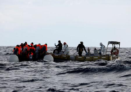 FILE PHOTO: Italian Navy personnel rescue migrants from their overcrowded raft, as lifeguards from the Spanish NGO Proactiva Open Arms rescue all 112 on aboard, including two pregnant women and five children, as it drifts out of control in the central Mediterranean Sea, some 36 nautical miles off the Libyan coast January 2, 2017. REUTERS/Yannis Behrakis/File Photo