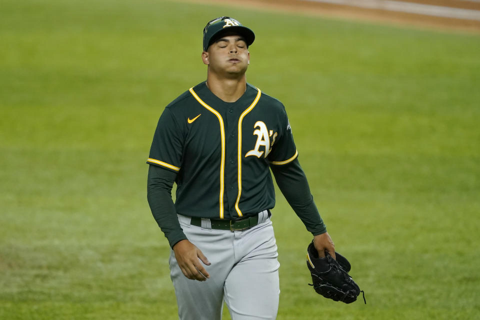 Oakland Athletics starting pitcher Jesus Luzardo lets out a deep breath as he walks to the dugout after being pulled in the seventh inning of a baseball game against the Texas Rangers in Arlington, Texas, Monday, Aug. 24, 2020. (AP Photo/Tony Gutierrez)