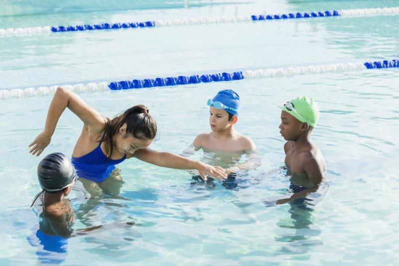 Young woman giving swim lessons to kids in a pool