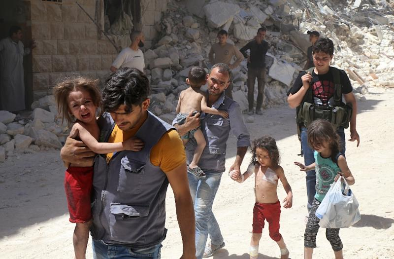 Syrian men carry injured children amid the rubble of destroyed buildings following air strikes in Aleppo on July 25, 2016 (AFP Photo/Baraa Al-Halabi)