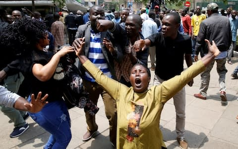 Supporters of opposition leader Raila Odinga cheer outside court - Credit: BAZ RATNER/Reuters