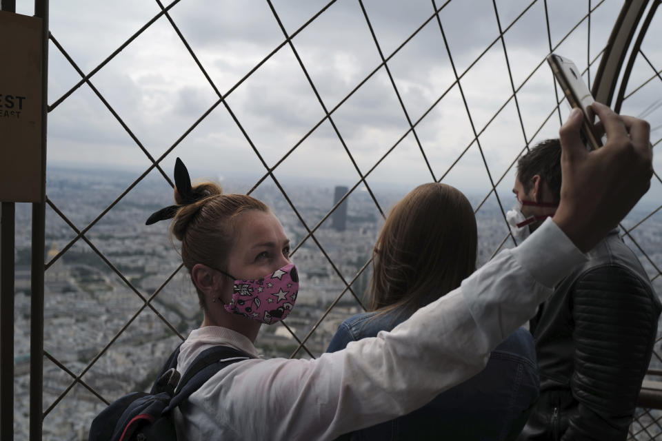 French visitor takes a selfie from the third level during the opening up of the top floor of the Eiffel Tower, Wednesday, July 15, 2020 in Paris. The top floor of Paris' Eiffel Tower reopened today as the 19th century iron monument re-opened its first two floors on June 26 following its longest closure since World War II. (AP Photo/Francois Mori)