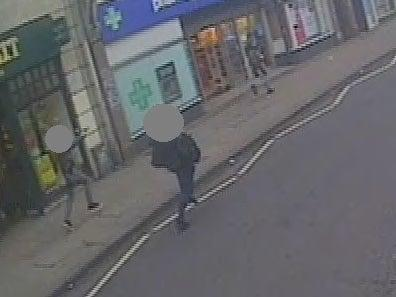 A CCTV still showing undercover armed police officers chasing Sudesh Amman, right, with their guns drawn after he stabbed two people in the Streatham attack (Metropolitan Police)