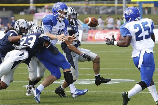 Central Connecticut State quarterback Andrew Clements (1) passes the ball to Darius Lee (25) while under pressure from New Hampshire's Keith Parkinson (33) in the first half of their NCAA college football game,Saturday, Sept. 15, 2012,in Durham, N.H. (AP Photo/Cheryl Senter)